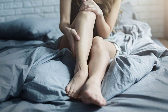Woman holding leg in bed. Lyme symptoms, joint pain and chronic fatigue.