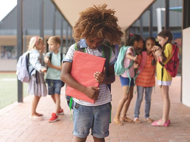 Front view of an African ethnicity schoolboy holding a red book in arms while he is looking down ground with classmates pointing in background in outside corridor at school