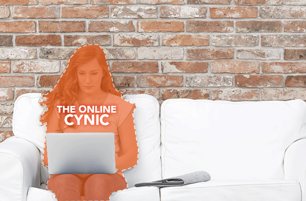 young woman with laptop sitting on white couch. brick wall. Woman labeled as the online cynic