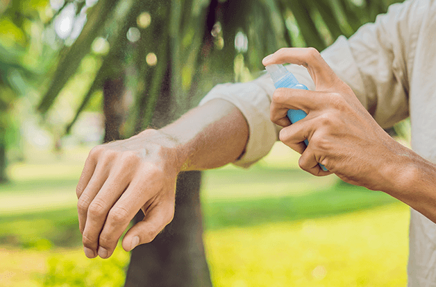 man spraying natural tick repellant on his skin, outdoor background