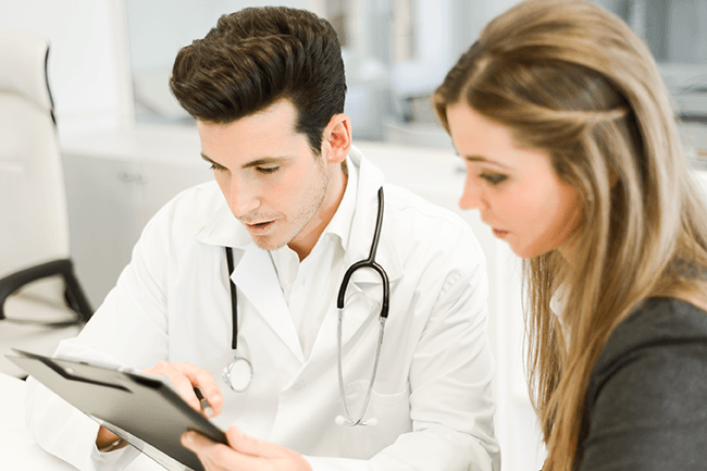 male doctor explaining medical clipboard to young adult female, in doctors office