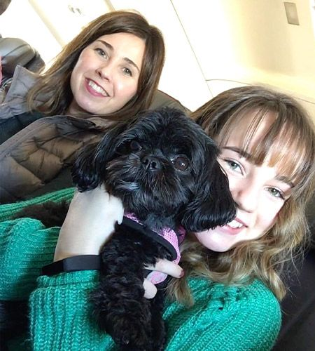 Jennifer, her daughter, and dog sitting in a plane