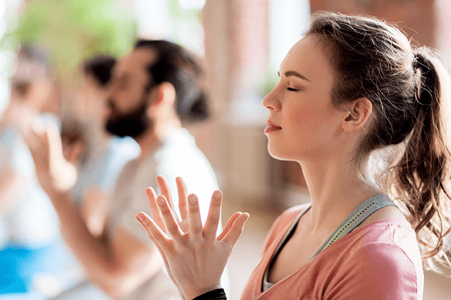 woman and blurred group meditating in a yoga studio