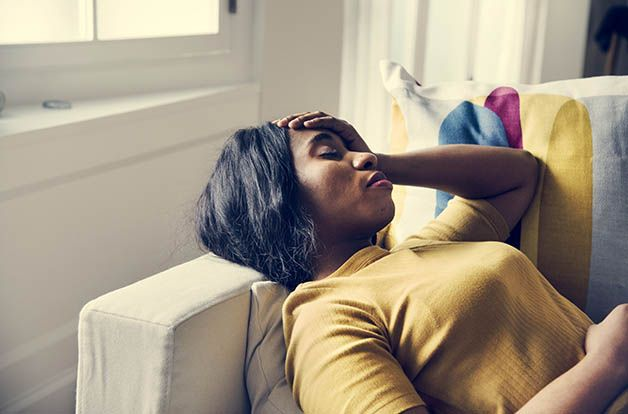 Black woman with a headache, placing a hand on her head while resting on the couch