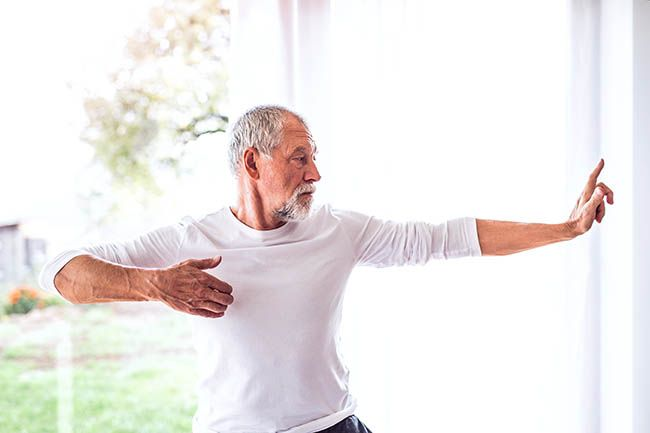 Active senior man doing gentle exercise at home.