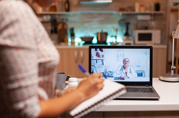 Doctor explaining diagnosis during a video conference with patient at midnight. Physician giving consultation to sick patient from hospital office during virtual examination, screen, medicine, appointment.