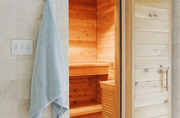 inside of heat sauna with a bucket of brushed and towels