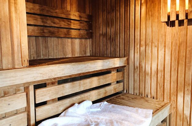 inside of a wooden infrared sauna, towel on seating