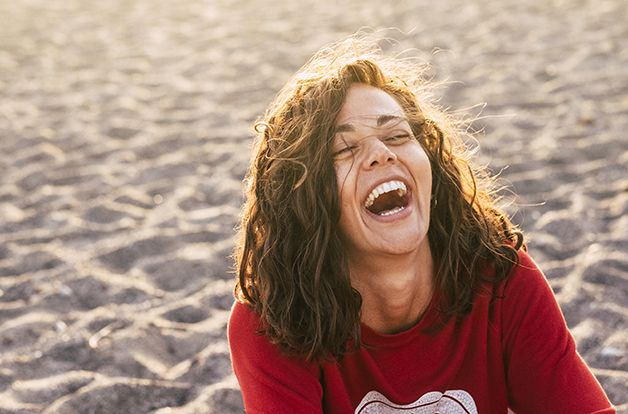 bright picture of laughing woman on the beach. backlight sunlight in nbackgroiund. beautiful young female model laugh like crazy. happiness and joyful concept for people in wanderlust