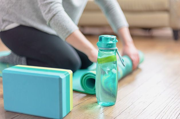 woman in comfy clothes, rolling up yoga mat in living room