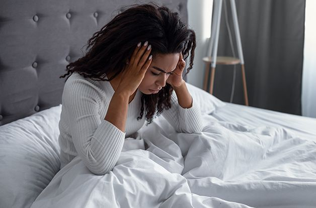 Young black woman suffering from headache or migraine after waking up in morning. Stressed lady sitting in bed with painful face expression feeling terrible hangover, unpleasant weakness, dizziness