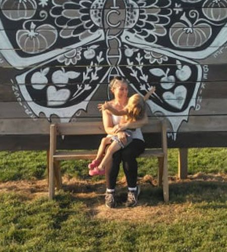 Trish holding a child while sitting on a bench